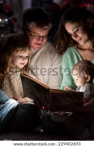 Family on Christmas Eve under the Christmas tree by the fireplace reading a book to their children with tales - stock photo