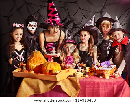 Family on Halloween party with children making carved pumpkin. - stock photo