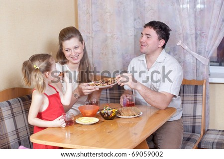 Family on kitchen behind a table - stock photo