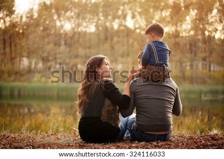 family on the banks of the river in the fall - stock photo