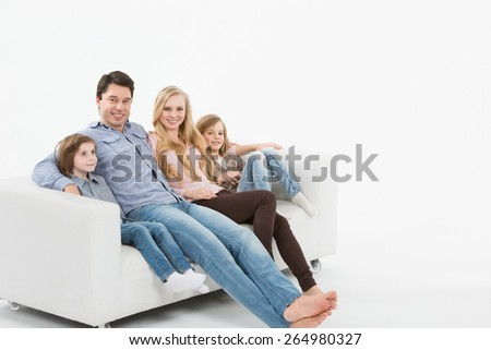 Family on the couch watching TV - stock photo