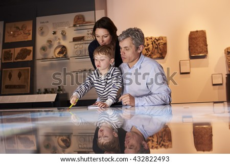 Family On Trip To Museum Looking At Map Together - stock photo