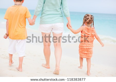 Family on tropical vacation walking along the beach - stock photo