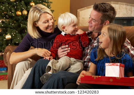 Family Opening Presents In Front Of Christmas Tree - stock photo