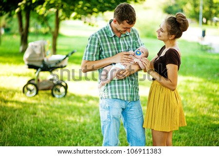 family outdoors in park, soft focus (focus on eyes of baby and mother) - stock photo