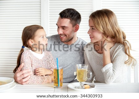 family, parenthood, communication and people concept - happy mother, father and little girl having dinner and talking at restaurant or cafe - stock photo