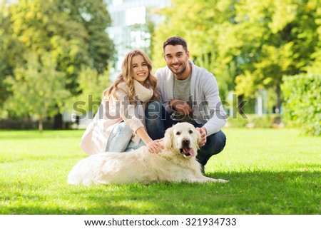 family, pet, animal and people concept - happy couple with labrador retriever dog walking in city park - stock photo