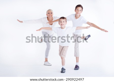 Family photo. Beautiful blonde mother exercising with two young sons, smiling. - stock photo