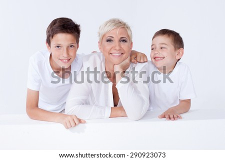 Family photo. Beautiful blonde mother posing with two young boys, looking at camera. - stock photo