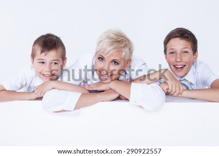 Family photo. Beautiful blonde mother posing with two young boys, smiling. - stock photo