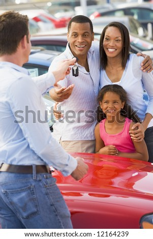 Family picking up new car from salesman - stock photo