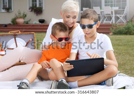 Family picnic. Beautiful mother with sons enjoying sunny day. Outdoor photo. - stock photo