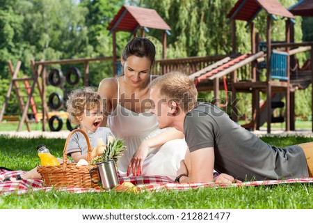 Family picnic on the playground during sunny day - stock photo