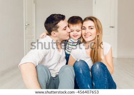 Family picture of two young parents playing with their boy child. They sit on the floor and the kid is between his parents. They wear white t-shirt and jeans. - stock photo