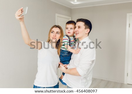 Family picture of two young parents playing with their boy child. They stand close together and the kid is in father's arms. They wear white t-shirt and jeans. Mom takes a selfie on the smartphone. - stock photo