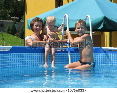 family play in collapsible pool - stock photo