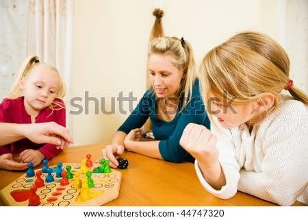 Family playing a board game at home in their leisure time, the setting is their living room - stock photo