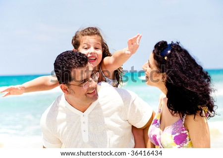 Family playing around on the beach - stock photo