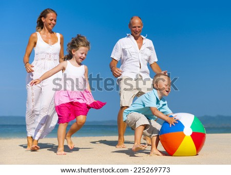 Family playing ball on beach. - stock photo