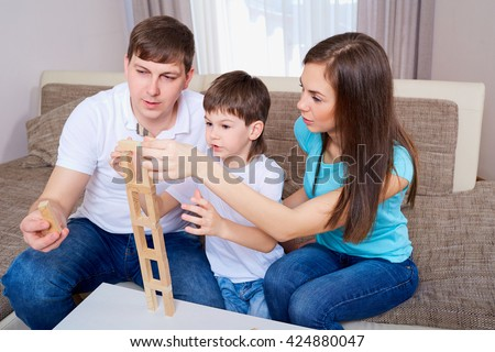 Family playing board game at home.Mom,father and son. - stock photo