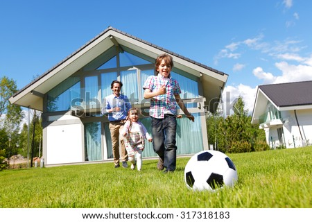 family playing football in front of their house - stock photo