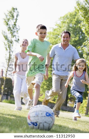 Family playing football in garden - stock photo