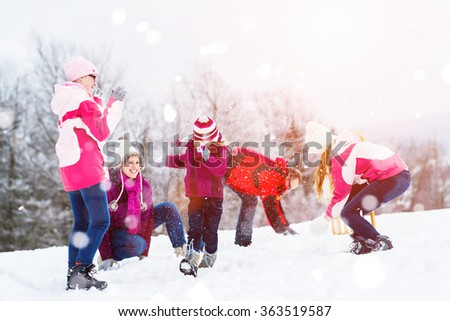 Family playing in snow having fight with snowballs - stock photo