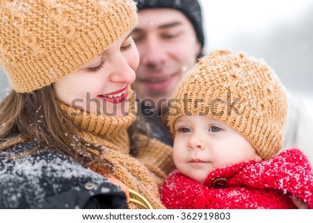 Family playing in the park in winter - stock photo