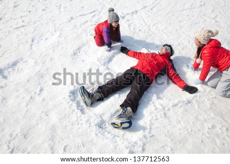 Family Playing in the Snow, Father Making Snow Angel - stock photo