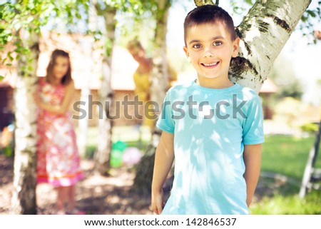 Family playing on grass in the back yard - stock photo