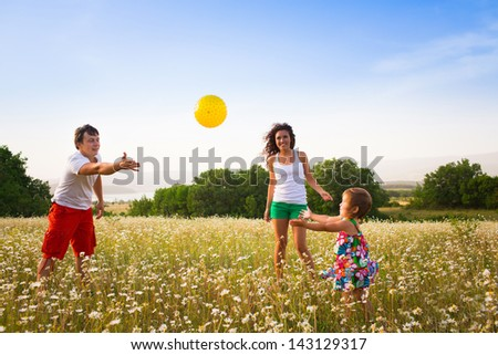 Family playing on the camomile meadow - stock photo