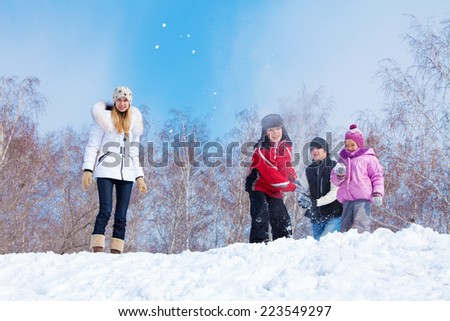 Family playing snowball. Parents with children walking at winter park - stock photo