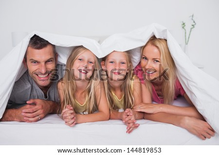 Family playing under the quilt in bed - stock photo