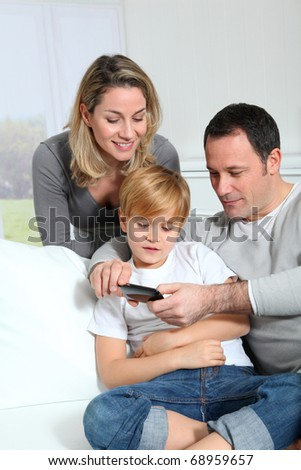 Family playing video game on smart-phone - stock photo