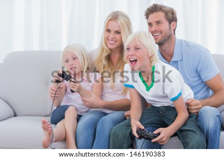 Family playing video games in the living room - stock photo