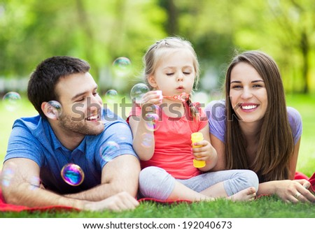 Family playing with bubbles outdoors - stock photo