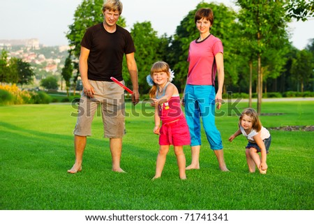 Family playing with frisbee in park - stock photo