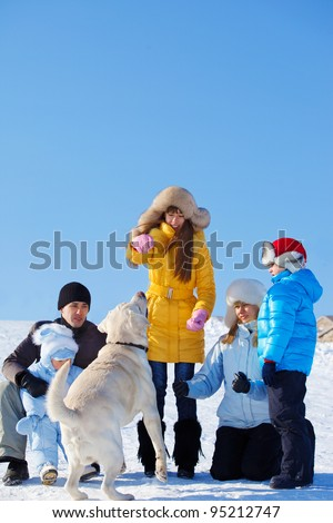 Family playing with Labrador dog in a winter park - stock photo