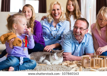 Family playing with toy blocks and a cat at home on the floor - stock photo