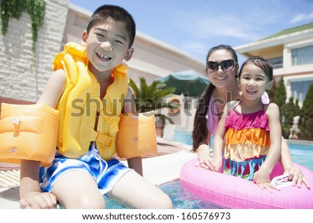 Family portrait by the pool with pool toys - stock photo