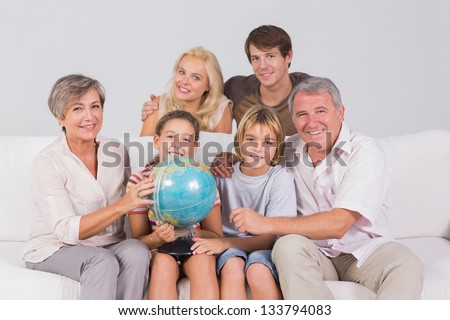 Family portrait looking at camera with a globe in sitting room - stock photo