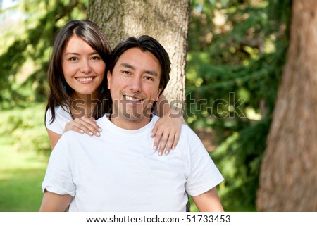 Family portrait of a brother and sister smiling outdoors - stock photo