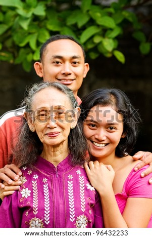 family portrait of asian ethnic elderly woman with young adult son and daughter - stock photo