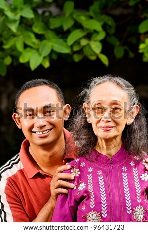 family portrait of asian ethnic senior woman with young adult son - stock photo