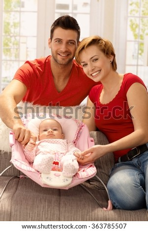 Family portrait of attractive young couple with newborn baby girl, smiling, looking at camera. - stock photo