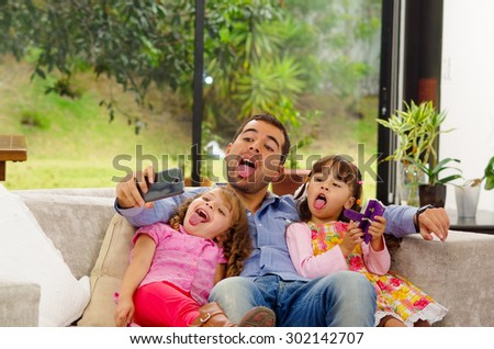 Family portrait of father and two daughters sitting together in sofa posing for selfie with their tongues out. - stock photo