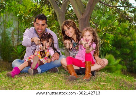 Family portrait of father, mother and two daughters sitting together in garden environment pointing forward towards camera. - stock photo