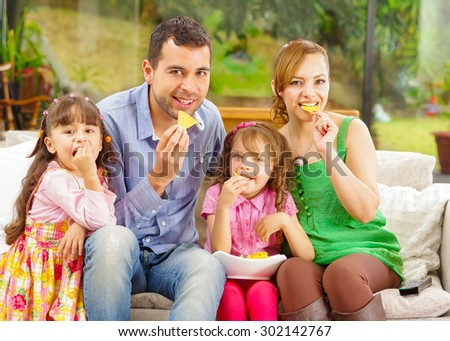Family portrait of father, mother and two daughters sitting together in sofa enjoying some nachos happily smiling to camera. - stock photo