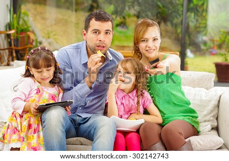 Family portrait of father, mother and two daughters sitting together in sofa playing with tablet while enjoying some nachos happily smiling to camera.. - stock photo