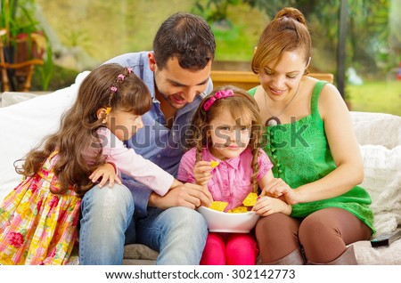 Family portrait of father, mother and two daughters sitting together in sofa sharing bowl with nachos on little girls lap . - stock photo